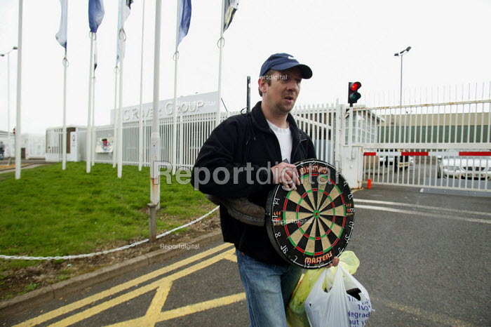Worker taking his dartboard and belongings. Workers leaving for the last time as MG Rover goes into receivership and 5000 are made redundant. MG Rover Group Longbridge Birmingham. - John Harris - 2005-04-15