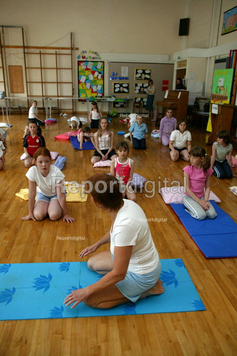 Alwynne Cartmell teaching yoga. Pupils exercising in a pre school morning Yoga class, Mytham CP School, Bolton. - John Harris - 2005-06-14