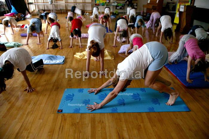 Alwynne Cartmell teaching yoga. Pupils exercising in a before school morning Yoga class, Mytham CP School, Bolton. - John Harris - 2005-06-14