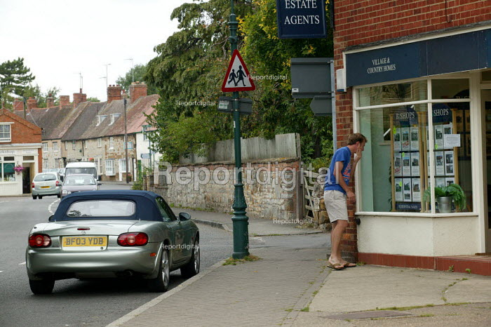 A young man looking at house prices in an estate agents window, Kineton village, Warwickshire. - John Harris - 2005-08-12