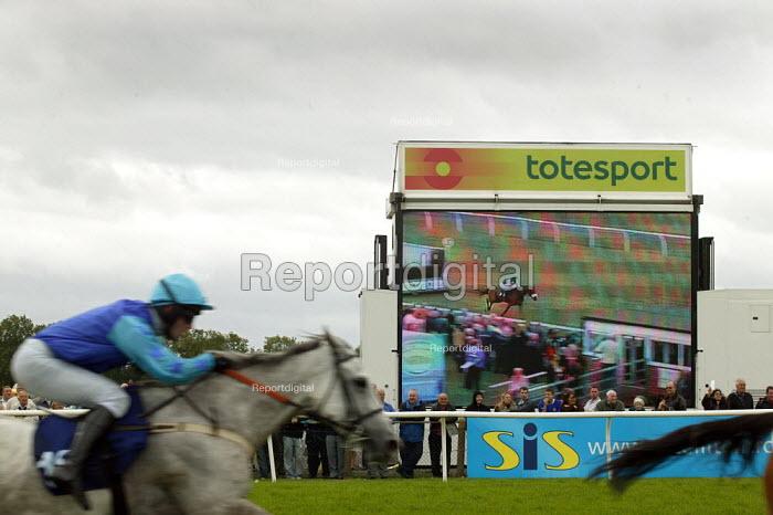 Horse and jockey pass the totesport display screen. Steeplechase racing at Stratford on Avon racecourse. - John Harris - 2006-09-02