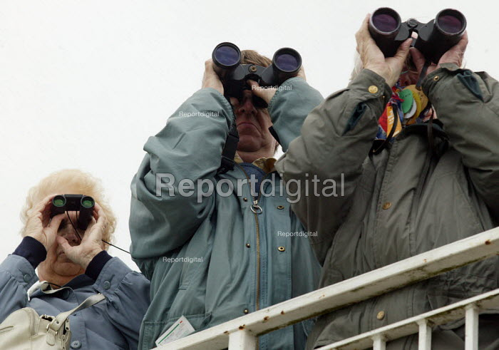Racegoers watching the race through binoculars. Steeplechase racing at Stratford on Avon racecourse. - John Harris - 2006-09-02