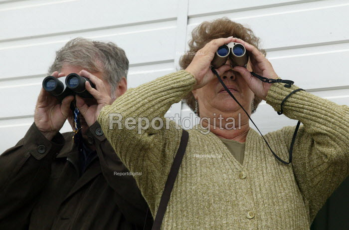 Racegoers watching the race through binoculars. Steeplechase racing at Stratford on Avon racecourse. - John Harris - 2006-09-02