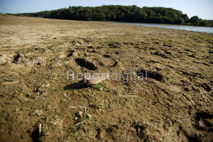 Water shortage. Low levels at Weir Wood reservoir, near East Grinstead. Southern Water. Discarded shoe and footprints in the cracked and dried up mud. - John Harris - 2006-09-10