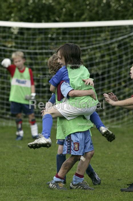 Primary school pupils playing football. Celebrating a goal - John Harris - 2006-10-18