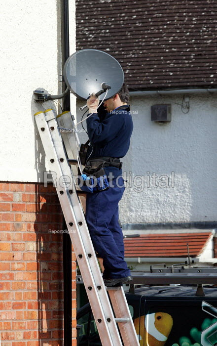 Worker installing a Sky Digital TV satellite dish to the side of a house. - John Harris - 2007-04-30