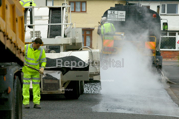 Workers re-surfacing a road in a residential area. Contractor Carillion Highway Maintenance working for Warwickshire County Council applying surface dressing of bitumen and stone chippings to the road to extend the life of the surface. The work is done seasonally. - John Harris - 2007-06-07