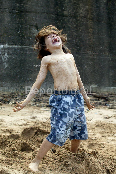 Small boy playing in sand on the beech, Staithes North Yorkshire. - John Harris - 2007-07-21