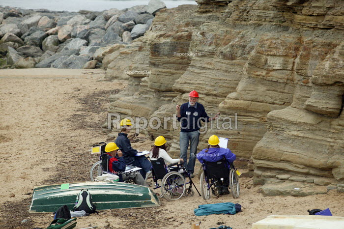Geologist lecturer from Durham University lecturing on the Jurassic coastline to disabled Open University students during a field trip, Staithes, North Yorkshire. - John Harris - 2007-07-21