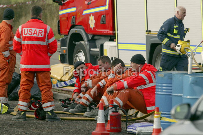 Exhausted USAR officers take a break. The search for the missing firefighters and look for clues to what caused the fire at a suspected arson at a warehouse in Warwickshire. Four firefighters are believed to have died tackling the blaze. Packhouse at Bomfords Ltd Atherstone Industrial Estate, Stratford upon Avon. - John Harris - 2007-11-05