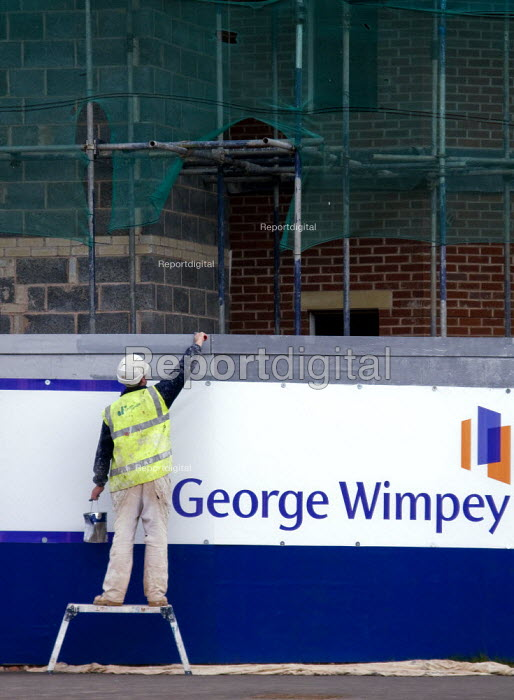A construction worker painting the fence on a building site where new houses are being built. - John Harris - 2008-03-06