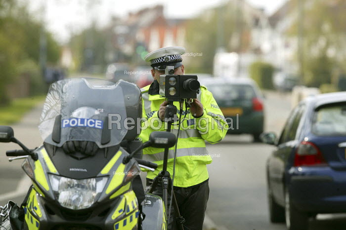 A Police officer monitoring traffic using a motorcycle based mobile speed camera as pupils walk past on their way home from school. Stratford upon Avon, Warwickshire. - John Harris - 2008-04-03