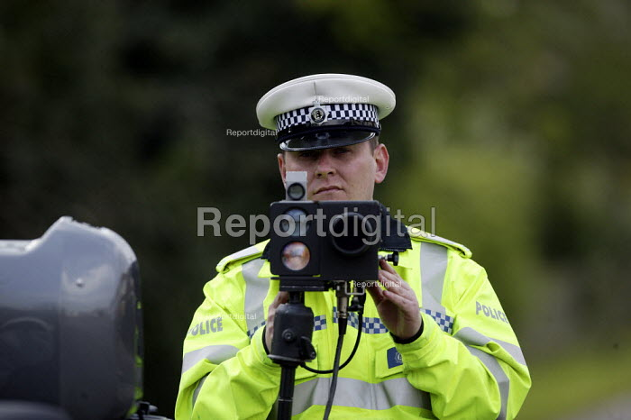 A Police officer monitoring traffic using a motorcycle based mobile speed camera, Stratford upon Avon, Warwickshire. - John Harris - 2008-04-03