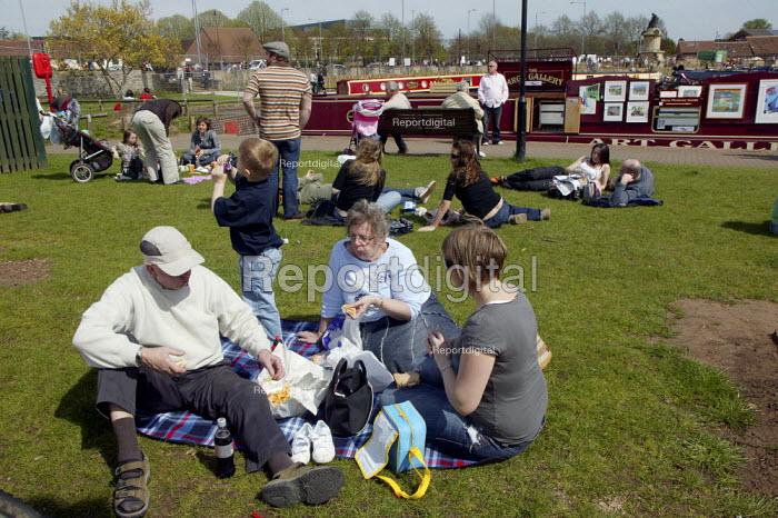 Tourists visiting Stratford upon avon eating a picnic on waterside. - John Harris - 2008-04-22
