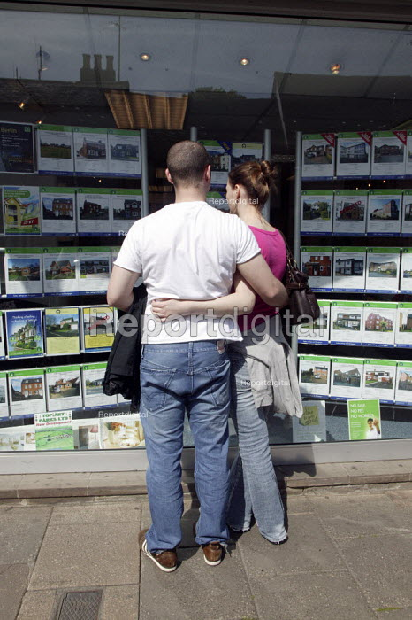 A young couple looking at house prices in an estate agents window. - John Harris - 2008-04-22