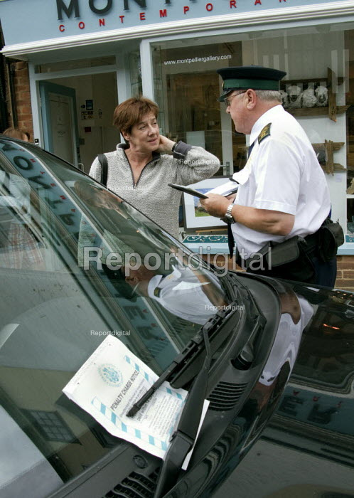 Driver arguing with a parking attendant who has just issued a ticket for exceeding the time allowed. - John Harris - 2008-07-12