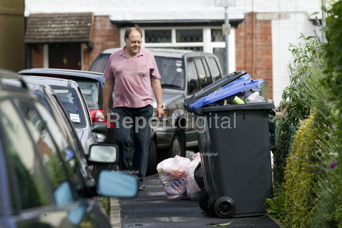 A man walks past rubbish recycling bins on the street outside a rented house of multiple occupancy. - John Harris - 2008-08-08