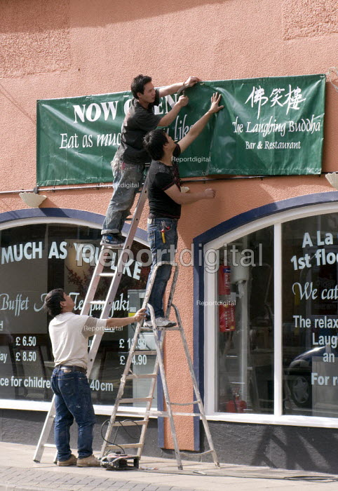 Migrant workers putting up a sign at a new Chinese restaurant. - John Harris - 2008-08-04