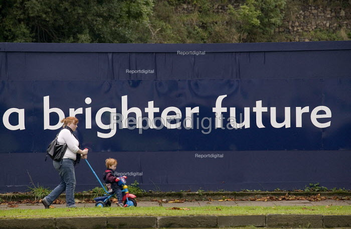 A mother and child passing a sign A Brighter Future, 750m regeneration plan for the old MG Rover car factory, Longbridge redevelopment site, Birmingham - John Harris - 2008-09-11