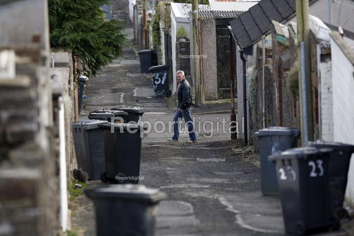 A man walking past a back alley. Merthyr Tydfil - John Harris - 2008-12-10