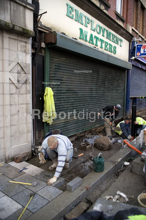 Construction workers working on a new pavement outside an employment agency called Employment Matters, Merthyr Tydfil - John Harris - 2008-12-10