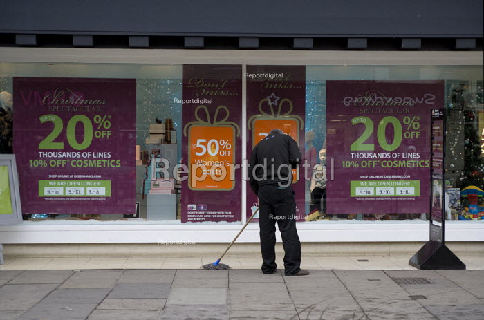 Agency worker cleaning infront of the store. Stratford on Avon. - John Harris - 2008-12-11