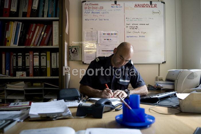Firefighter doing paperwork at Perry Barr Fire station Birmingham. - John Harris - 2009-04-17