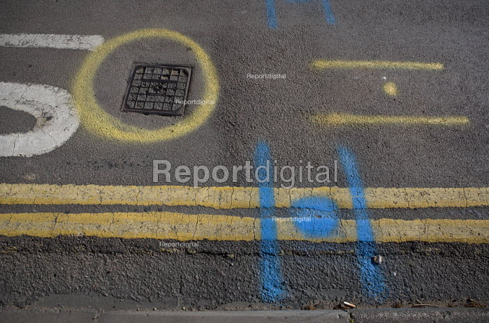 Markings on the road surface showing the location of utilities underground prior to roadworks. Due to the huge number of utility services located within the roads and pavements, it often becomes necessary to indicate what is where. This is done by reading utility plans and using a spray paint to show the mapped location of each service using signs, letters, and colours on the pavements. These show the intricate networks of pipes, cables, and wires that constitute the space under the pavement in an urban environment. - John Harris - 2009-05-08
