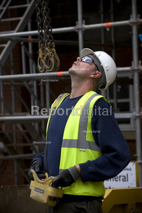 A radio remote control crane operator moving materials. Building site, Warwickshire. - John Harris - 2009-07-24