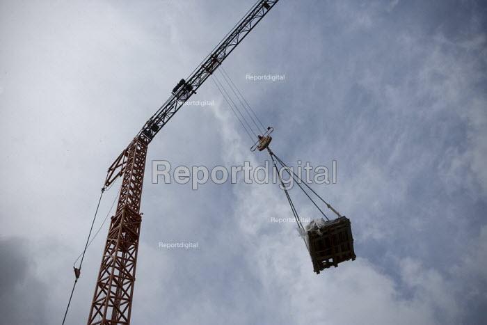 A radio remote control crane operator moving materials. Building site, Warwickshire. - John Harris - 2009-07-24