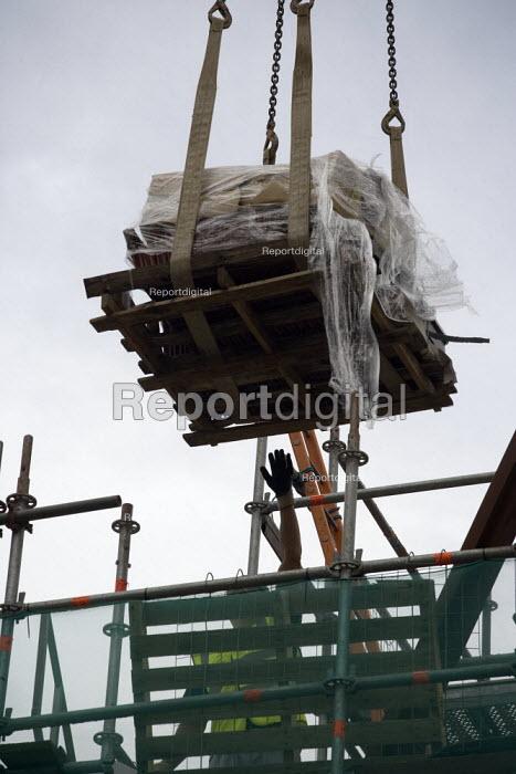 A Polish banksman assisting remote control crane to move materials with hand signals. Building site, Warwickshire. - John Harris - 2009-07-24