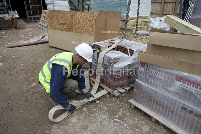 A remote control crane operator moving materials, putting straps around a pallet. Building site, Warwickshire. - John Harris - 2009-07-24