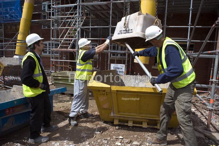 A Polish banksman assisting remote control crane to move materials. Building site, Warwickshire. - John Harris - 2009-07-24