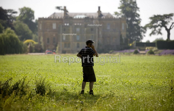 A Farmworker talking on his mobile phone on a country estate in Warwickshire. - John Harris - 2009-07-02