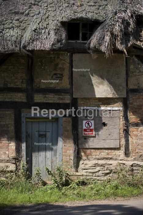 A derelict thatched cottage in a village, Warwickshire. - John Harris - 2009-07-02