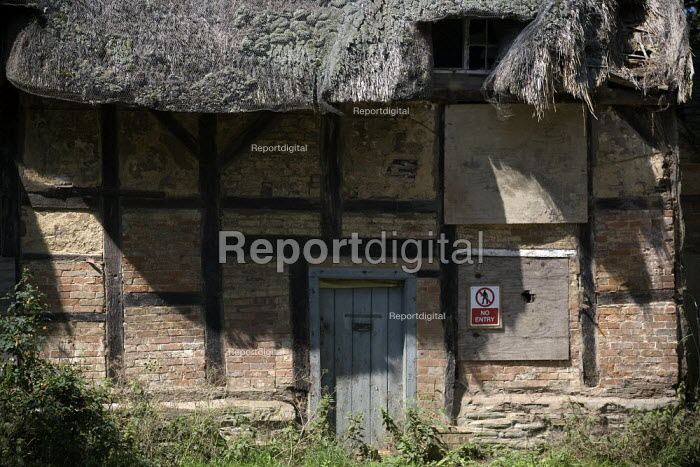 A derelict thatched cottage in a village, Warwickshire. - John Harris - 2009-07-02