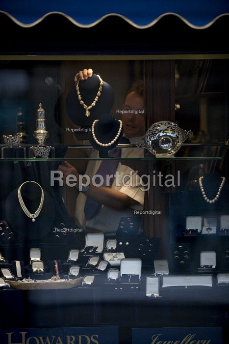 A shopworker carefully removing an expensive Freshwater pearl and diamond necklace from the shopwindow display of silver and diamond jewellery. Howards Jewellers, Stratford on Avon. - John Harris - 2009-07-15