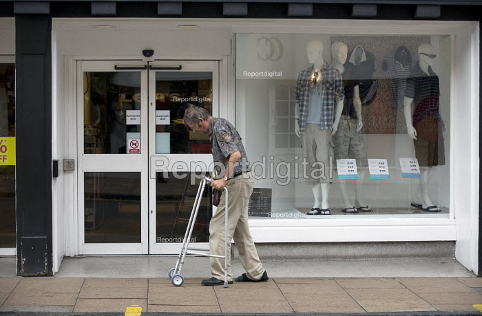 Disabled schizophrenic with a zimmer frame making his way along the High Street past a clothing shop. Stratford on Avon. - John Harris - 2009-07-15