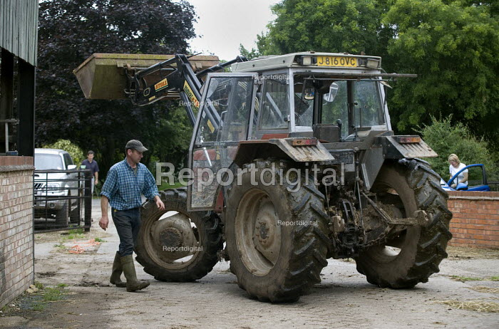 A farmworker getting into his tractor in a farmyard in Warwickshire. - John Harris - 2009-07-22