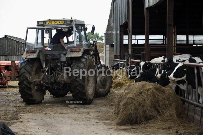 A farmworker getting into his tractor in a farmyard in Warwickshire. - John Harris - 2009-07-22