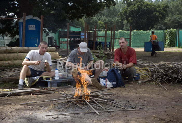 Polish workers take a lunch break from the runner beans, cooking their food on an open fire, Warwickshire. - John Harris - 2009-07-23