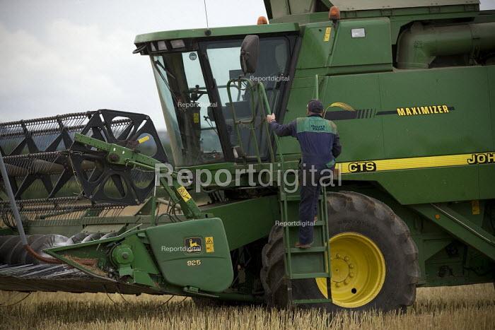 Combine harvester driver beginning the oilseed rape harvest. Warwickshire. - John Harris - 2009-07-20