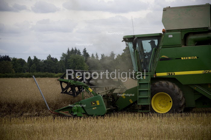 Combine harvester driver beginning the oilseed rape harvest. Warwickshire. - John Harris - 2009-07-20