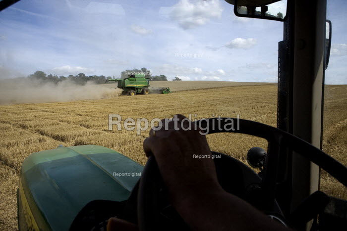 Tractor driver in his cab. Harvesting wheat on a farm in Worcestershire - John Harris - 2009-08-08