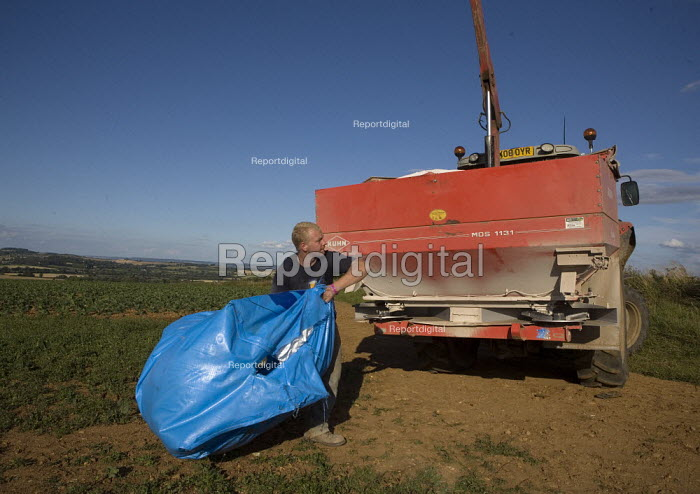 A farmworker loading the chemical fertiliser spreader on a tractor in the Cotswalds. - John Harris - 2009-07-25