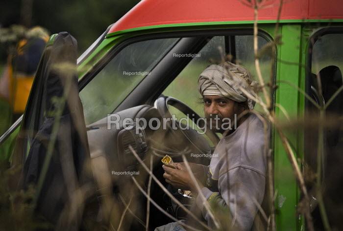 A farmworker eats lunch in the van, taking a break from picking peas in a field on a farm in the Cotswalds - John Harris - 2009-08-05