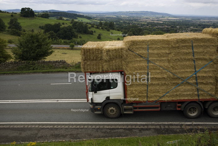 A heavily loaded lorry carrying straw bales braking hard as descends a steep hill in the Cotswolds - John Harris - 2009-08-05
