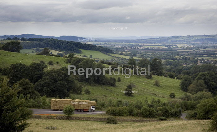 A heavily loaded lorry carrying straw bales descending a steep hill in the Cotswolds - John Harris - 2009-08-05