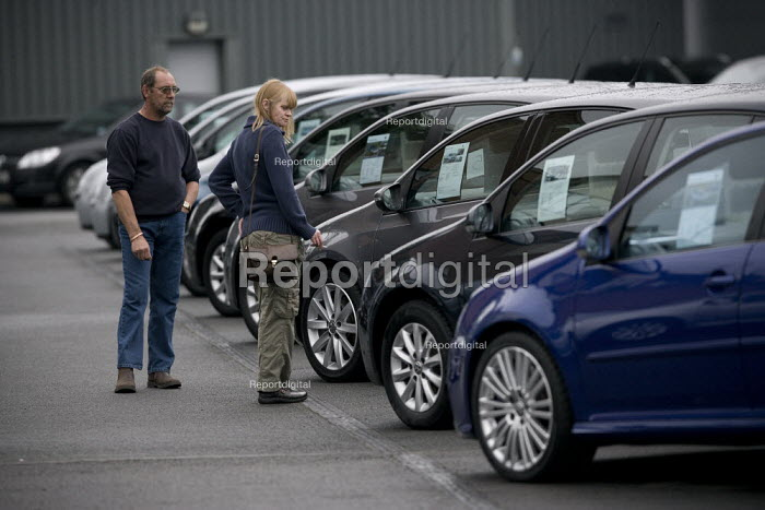 Discerning customers looking at used cars on a dealers forecourt. - John Harris - 2009-08-01