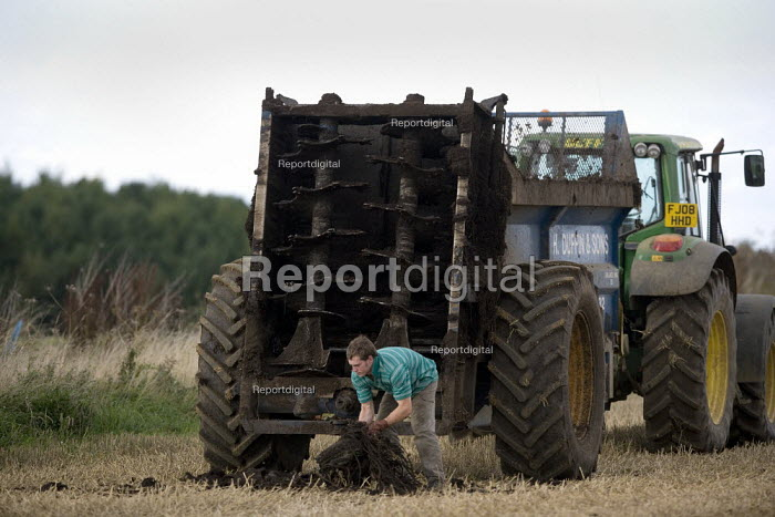 Subcontractors cutting out twine that has become tangled in the rotating blades of their muck spreaders. Rutland. - John Harris - 2009-08-21